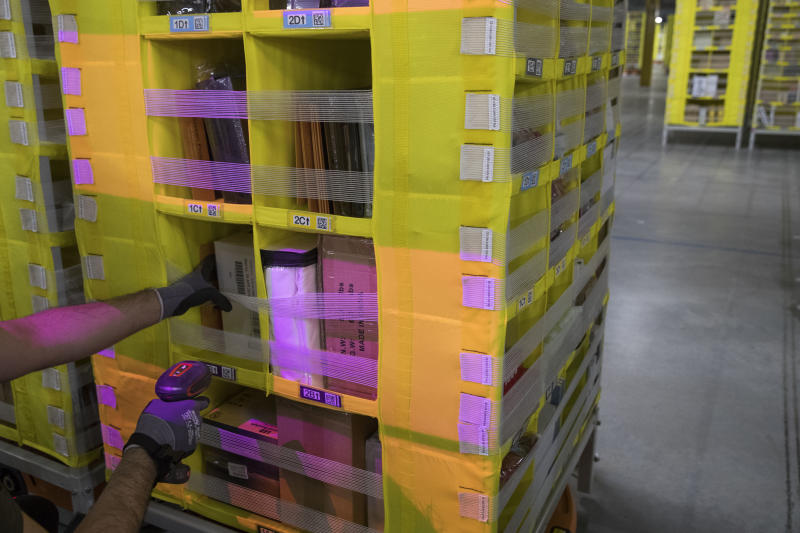 "In this Dec. 5, 2018, photo Amazon Stower Leo Esparragoza uses colored light to help sort merchandise into pods at the Amazon fulfillment center on Staten Island borough of New York. Amazon's ""Prime Day"" is back. The made-up holiday, first launched in 2015, has become one of Amazon's busiest shopping days, offering discounts on gadgets, TVs and other goods. (AP Photo/Mary Altaffer)"