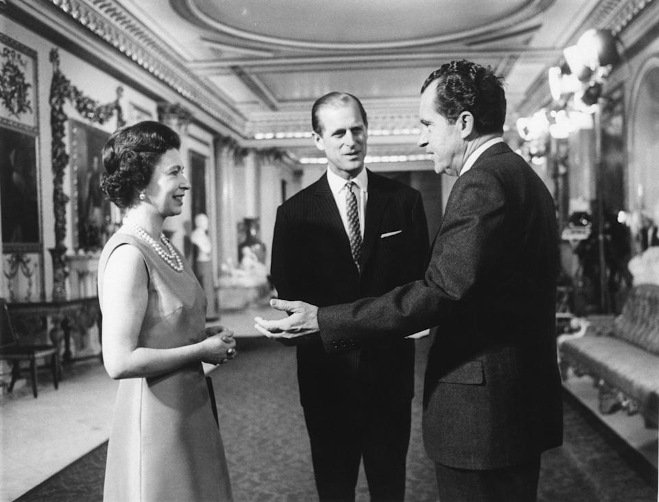President Nixon speaks with Queen Elizabeth II and Prince Philip at Buckingham Palace.