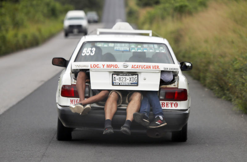 In this Nov. 3, 2018 photo, Central American migrants, part of the caravan hoping to reach the U.S. border, a ride on in the trunk of a taxi, in Acayucan, Veracruz state, Mexico. (AP Photo / Marco Ugarte)