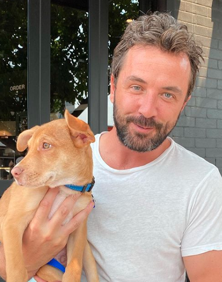 Darren McMullen poses with a dog in a blue collar