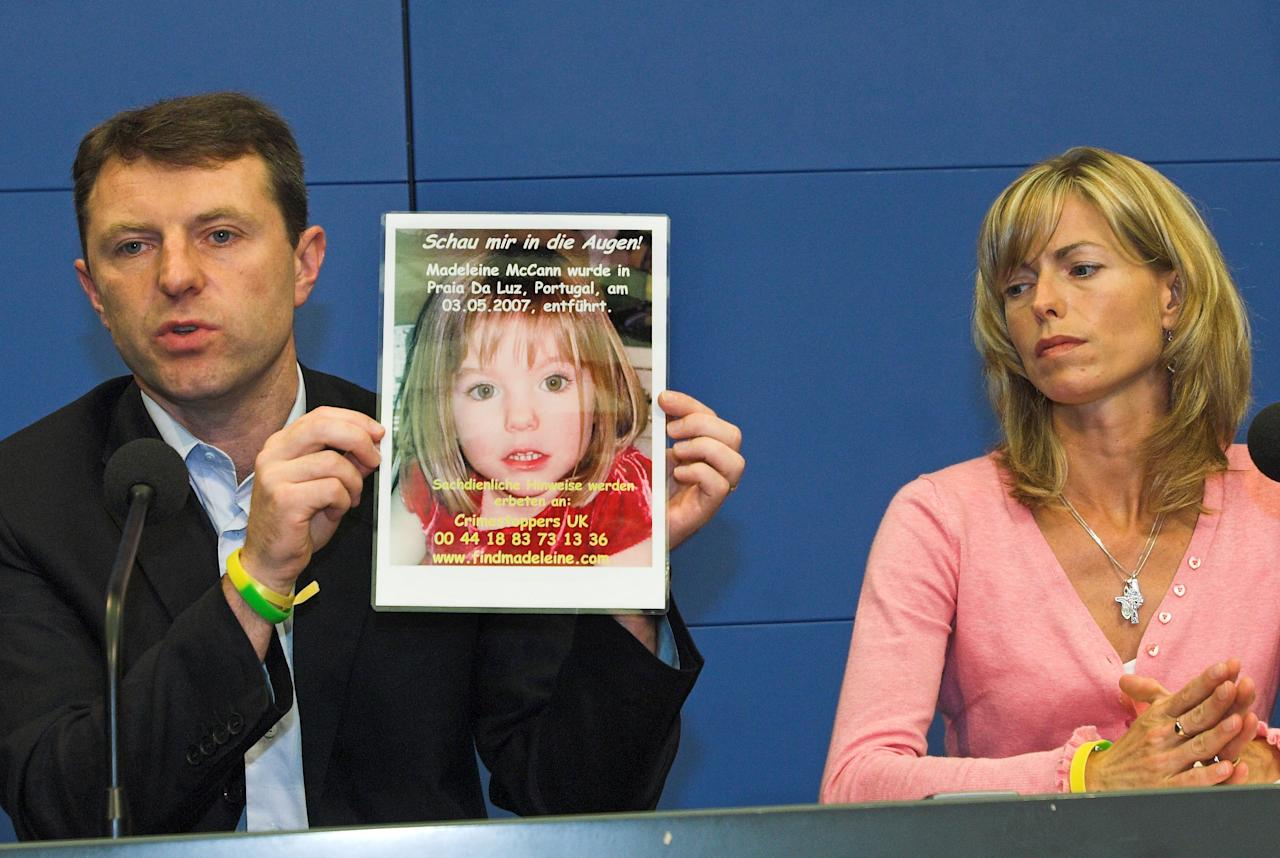 Gerry, left, and Kate McCann, parents of four years old Madeleine McCann, missing in the Portuguese town of Praia Da Luz since May, present a picture of their daughter during a press conference in Berlin, Wednesday, June 6, 2007. The parents of missing Madeleine McCann on Wednesday March 19, 2008 accepted an apology and more than $1 million in damages over tabloid newspaper stories suggesting they had caused their daughter's death. (AP Photo/Sven Kaestner, FILE)
