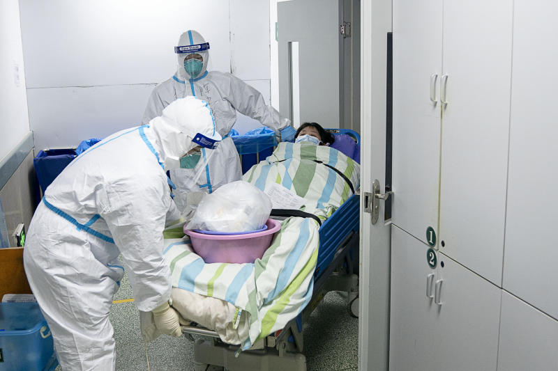 Medical workers transfer a patient out of the intensive care unit at hospital in Wuhan. Source: AP