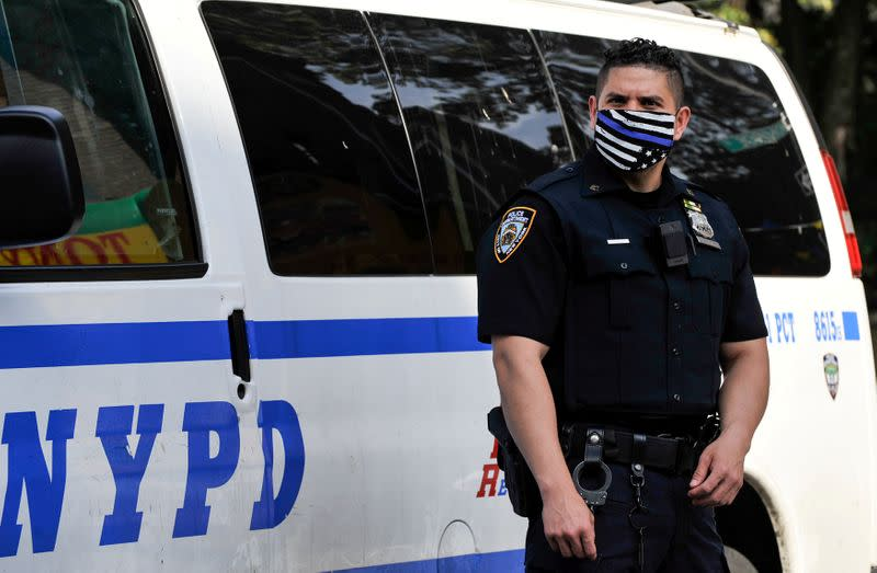 A NYPD police offer wears a Blue Line facemask at the scene of a shooting