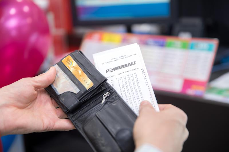 A Powerball Quickpick ticket being removed from a wallet.
