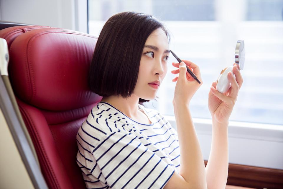Commuter makeup rituals are a cause of debate for some. [Photo: Getty]