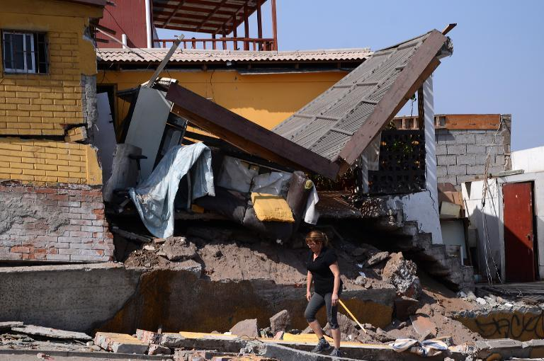 A woman walks next to a destroyed house in Iquique, northern Chile, on April 2, 2014 a day after a powerful 8.2-magnitude earthquake hit off Chile's Pacific coast