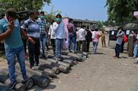 People queue to refill their oxygen cylinders for coronavirus patients at a centre in Moradabad
