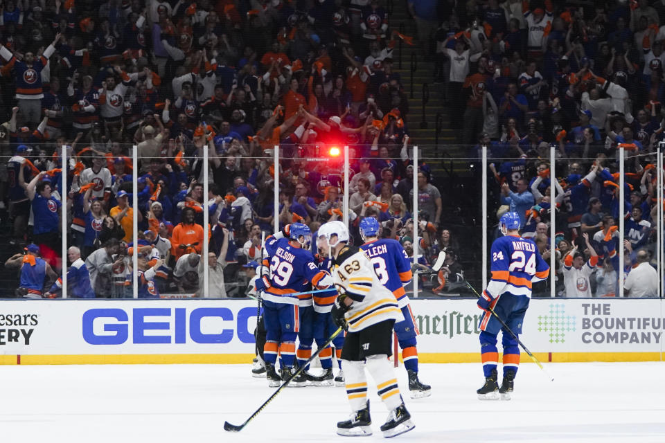 Boston Bruins' Brad Marchand (63) skates toward his bench as the New York Islanders celebrate a goal by Casey Cizikas during the third period of Game 4 during an NHL hockey second-round playoff series Saturday, June 5, 2021, in Uniondale, N.Y. (AP Photo/Frank Franklin II)