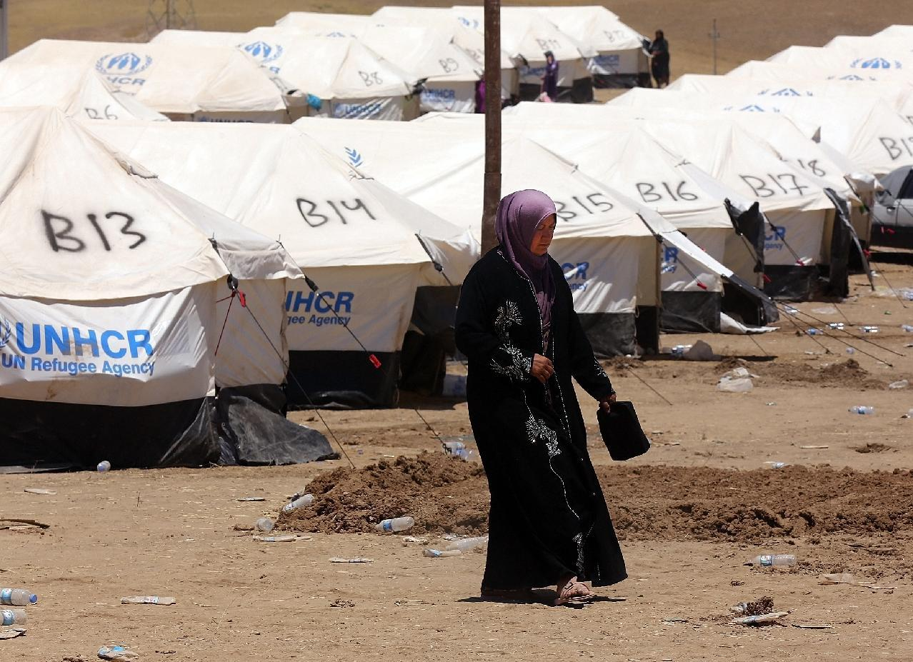 An Iraqi woman who fled the violence in her hometown of Mosul walks past tents at Khazir refugee camp outside of Irbil, 217 miles (350 kilometers) north of Baghdad, Iraq, Monday, June 16, 2014. Sunni militants captured a strategic city along the highway to Syria on Monday, moving closer to their goal of linking areas under their control on both sides of the border. The al-Qaida breakaway group leading the push in Iraq also is fighting in the civil war next door in Syria where it controls territory abutting the Iraqi border.(AP Photo)