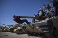 Students climb on a tank during a ceremony marking the annual Memorial Day to remember fallen soldiers and victims of terror, at the Armored Corps memorial site in Latrun, Israel, Wednesday, April 14, 2021. (AP Photo/Oded Balilty)