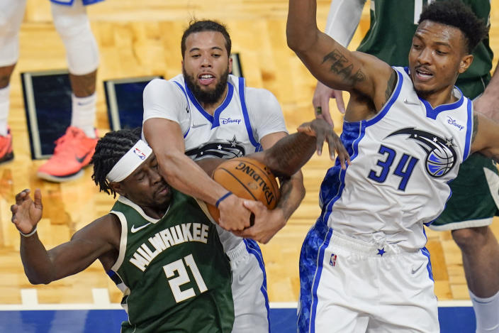 Milwaukee Bucks guard Jrue Holiday (21) goes after a rebound against Orlando Magic guard Michael Carter-Williams, center, and center Wendell Carter Jr. (34) during the second half of an NBA basketball game, Sunday, April 11, 2021, in Orlando, Fla. (AP Photo/John Raoux)