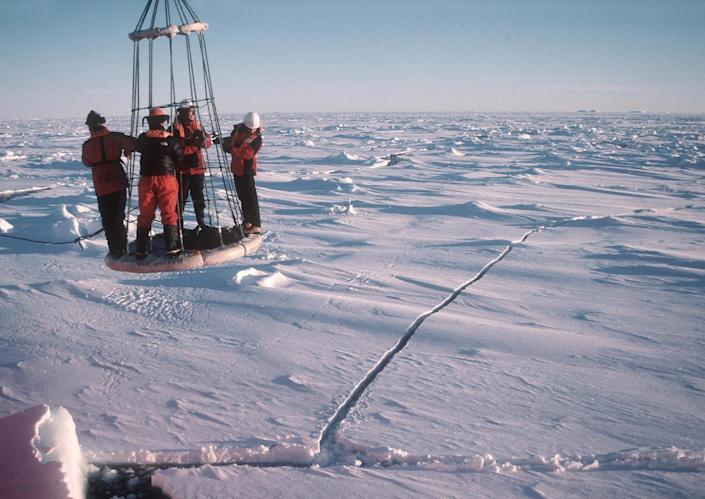 This handout photo provided by the British Antarctic Survey, taken in March 2003, shows four scientists being retrieved from research on sea ice in the Antarctic using a buoy. The ice goes on seemingly forever in a white pancake-flat landscape, stretching so far it just set a record. And yet in this confounding region of the world, that spreading ice may be a cock-eyed signal of man-made climate change, scientists say. (AP Photo/David Vaughan, Bristish Antarctic Survey)