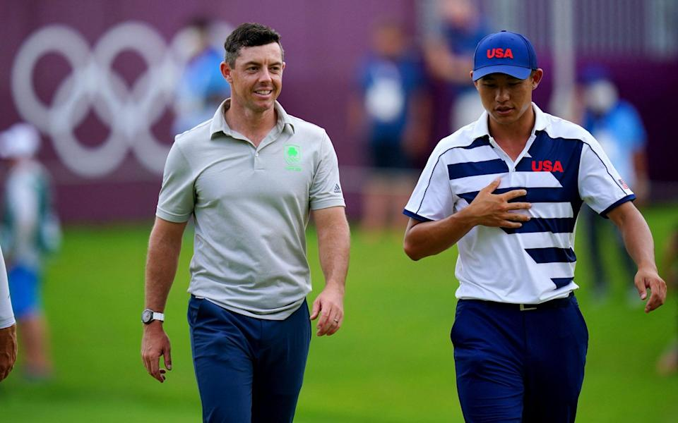 Ireland's Rory Mcilroy (L) and USA's Collin Morikawa (R) walk after hole out in round 1 of the mens golf individual stroke play during the Tokyo 2020 Olympic Games at the Kasumigaseki Country Club in Kawagoe on July 29, 2021 - GETTY IMAGES