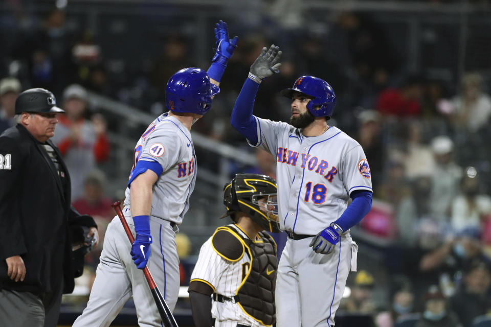 New York Mets' Jose Peraza (18) is congratulated by Billy McKinney, left, after hitting a solo home run in the fifth inning of the team's baseball game against the San Diego Padres on Saturday, June 5, 2021, in San Diego. (AP Photo/Derrick Tuskan)