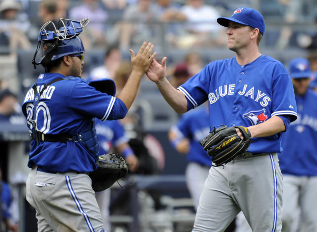 Toronto Blue Jays closer Casey Janssen, right, celebrates with catcher Dioner Navarro after they defeated the New York Yankees 6-4 in a baseball game on Saturday, July 26, 2014, at Yankee Stadium in New York. (AP Photo/Bill Kostroun)