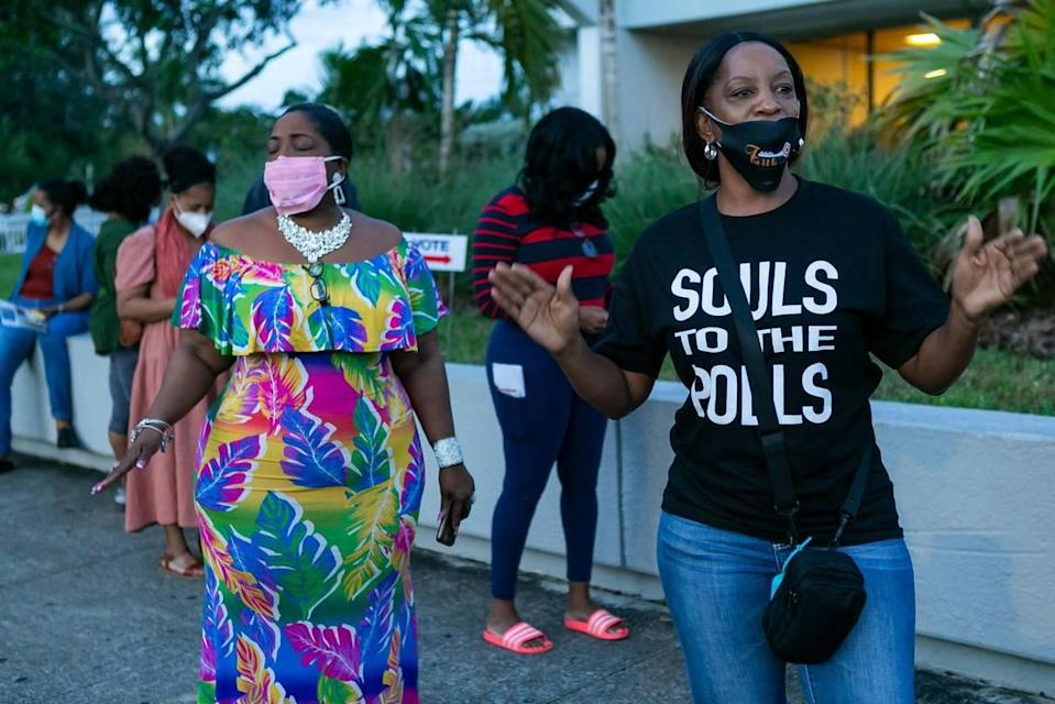 Pastor Stephanie E. Russell, right, and Denise Mills Mincey, left, pray as voters lineup to cast their early ballots at the North Dade Regional Library in Miami Gardens on Saturday, October 24, 2020. Faith in Florida, a federation of the national faith-based grassroots organization Faith in Action, hosted Prayer at the Polls events like this one across the state Saturday.