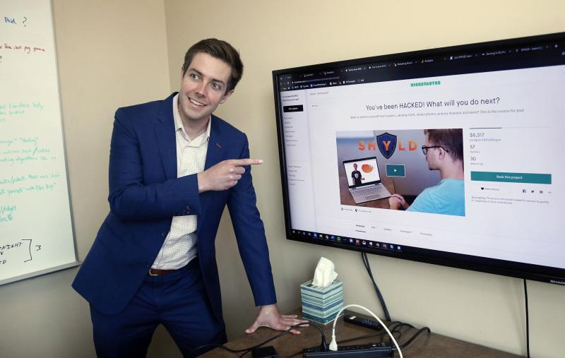 In this Aug. 27, 2019 photo, Tyler Olson poses in hits office at the University of St. Thomas - Minneapolis campus. Olson is just starting a cybersecurity company. (AP Photo/Jim Mone)