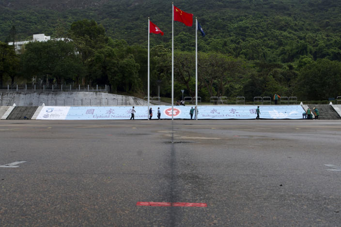 """A red marking sign for police march is seen in front of a Chinese national flag and a Hong King flag on the National Security Education Day at a police school in Hong Kong Thursday, April 15, 2021. Beijing's top official in Hong Kong on Thursday warned foreign forces not to interfere with the """"bottom line"""" of national security in Hong Kong, threatening retaliation even amid ongoing tensions between China and Western powers. (AP Photo/Vincent Yu)"""