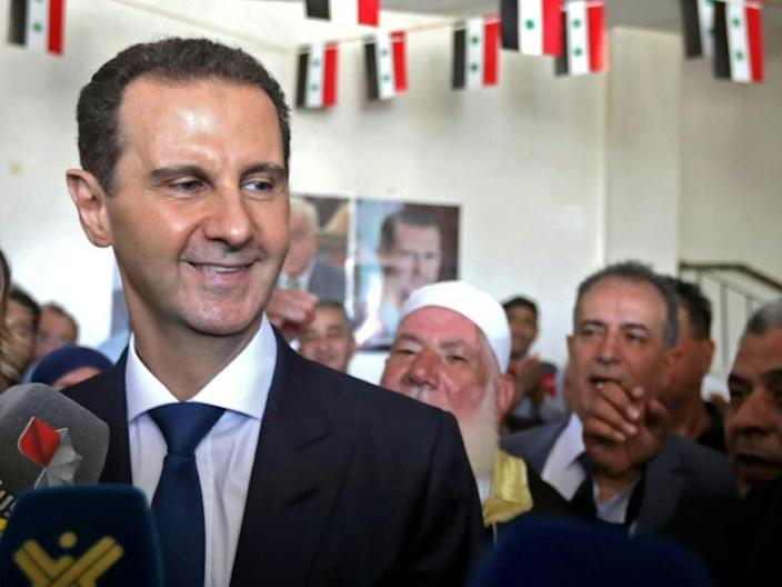 Assad greets supporters after casting his vote at a polling station near the capital Damascus on Wednesday