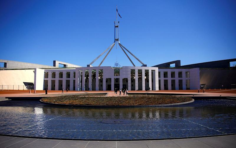 Tourists walk around the forecourt of Australia's Parliament House in Canberra - REUTERS