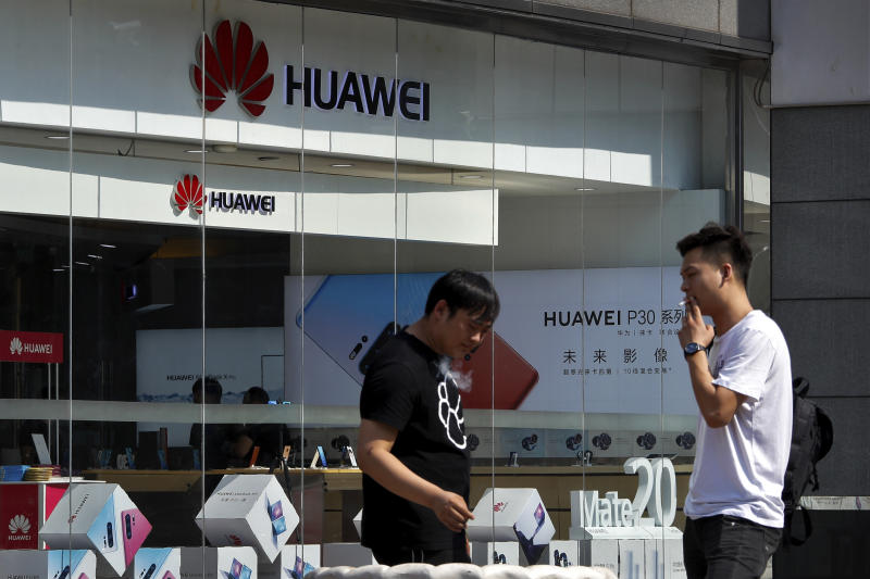 "People smoke near a Huawei retail store in Beijing, Tuesday, June 11, 2019. Chinese tech giant Huawei said Tuesday it would have become the world's number one smartphone maker by year's end if it were not for ""unexpected"" circumstances — a hint that pressure from the U.S. may be hurting its sales. (AP Photo/Andy Wong)"