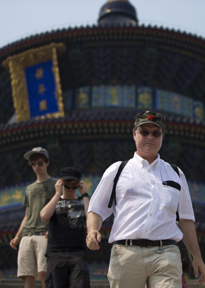 "In this Wednesday, July 31, 2013 photo, a foreign tourist wears a communist hat as he and others visit the Temple of Heaven in Beijing. China's new tourism slogan ""Beautiful China"" has been criticized by industry experts who say it illustrates a marketing problem that has led to a weakness in growth in foreign visitors over the past few years. (AP Photo/Andy Wong)"