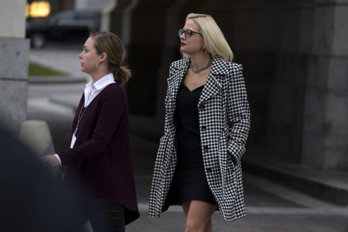 FILE - In this Feb. 5, 2020, file photo, Sen. Kyrsten Sinema, D-Ariz., departs after the impeachment acquittal of President Donald Trump, on Capitol Hill in Washington. More than her shock of purple hair or unpredictable votes Sinema is perhaps best known for doing the unthinkable in Washington: spending time on the Republican side of the aisle. Her years in Congress have been a whirlwind of political style and perplexing substance, an anti-war liberal-turned-deal-making centrist who now finds herself at the highest levels of power. (AP Photo/Jose Luis Magana, File)