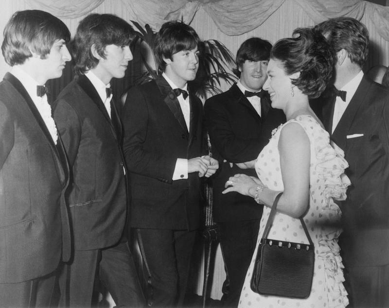 (Original Caption) Princess Margaret Meets Beatles, M.B.E. London: H.R.H. Princess Margaret, Countess of Snowdon and the Earl of Snowdon (hidden right), last night attended the Royal World Premiere of the Beatles new movie, Help!, which was held at the London Pavilion in aid of the Dockland Settlements and Variety's Charity Fund for Children. Before the film, the Beatles were presented to the Princess. Photo shows, Princess Margaret with the Beatles, from left to right, Ringo Starr, George Harrison, Paul McCartney and John Lennon.