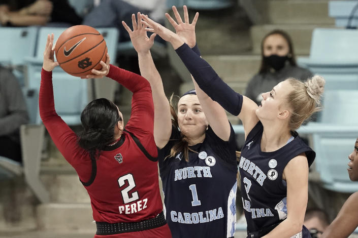 North Carolina State guard Raina Perez (2) shoots while North Carolina guard Alyssa Ustby (1) and guard Petra Holesinska (2) defend during the second half of an NCAA college basketball game in Chapel Hill, N.C., Sunday, Feb. 7, 2021. (AP Photo/Gerry Broome)