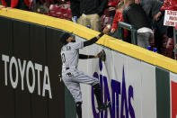 Chicago White Sox Billy Hamilton climbs the outfield wall to give the ball to a fan prior to the bottom of the sixth inning of a baseball game against the Cincinnati Reds, Tuesday, May 4, 2021 in Cincinnati. (AP Photo/Aaron Doster)