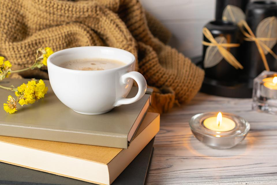 Hygge lifestyle still life composition with coffee, candles, books and knitted plaid on white wooden background