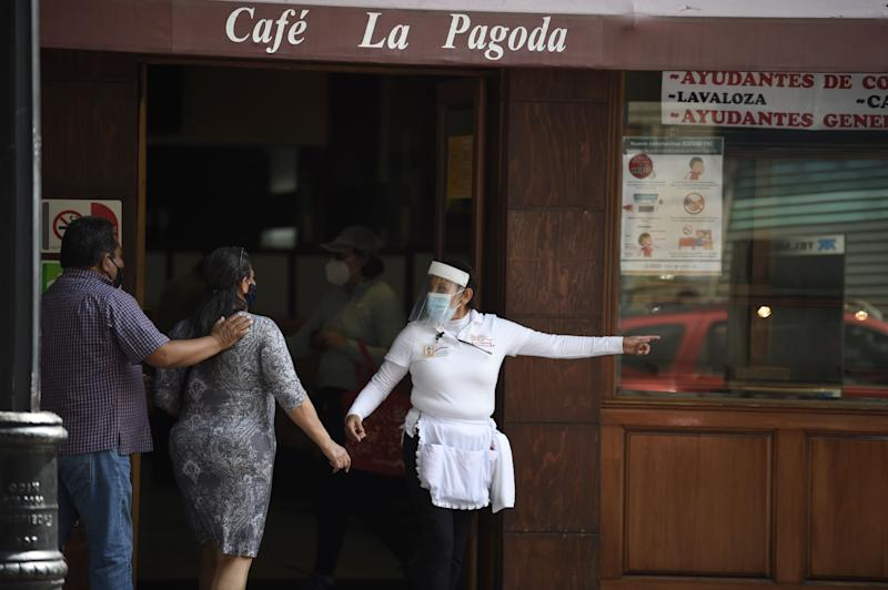 A restaurant employee interacts with customers in Mexico City on July 1, 2020 during the COVID-19 pandemic. - Starting this week Mexico City is allowing the reopening of restaurants, shops, street markets and athletic complexes but with limited capacity and hours. (Photo by Alfredo ESTRELLA / AFP) (Photo by ALFREDO ESTRELLA/AFP via Getty Images)