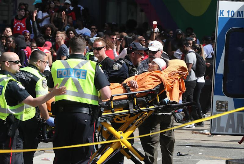 A woman with a head injury is stretchered into an ambulance. Source: Getty
