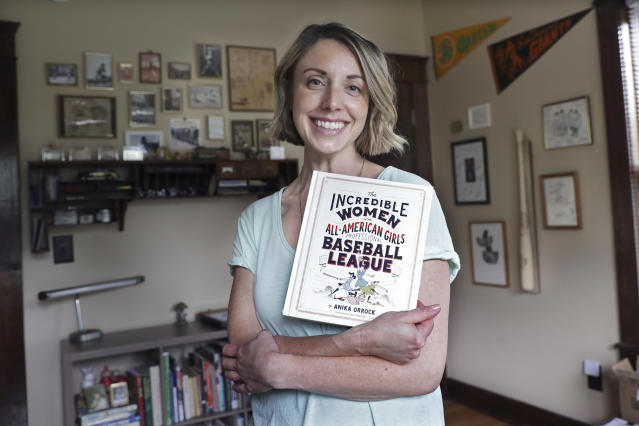 """This April 30, 2020, photo shows Anika Orrock with her book """"The Incredible Women of the All-American Girls Professional Baseball League"""" in her home in Nashville, Tenn. Because of the coronavirus pandemic, Orrock's appearance to throw out the first pitch at Yankee Stadium May 5 has been canceled, as well as her plans to travel for the book's promotion. (AP Photo/Mark Humphrey)"""