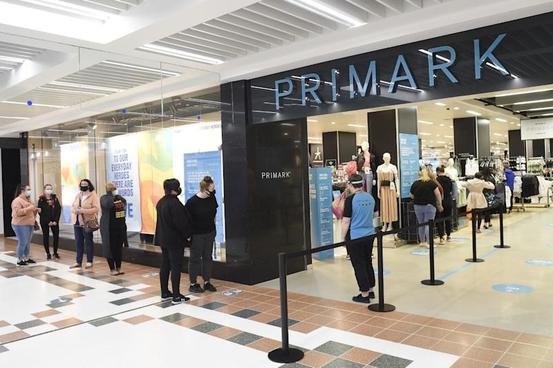 Shoppers queuing in shopping centre