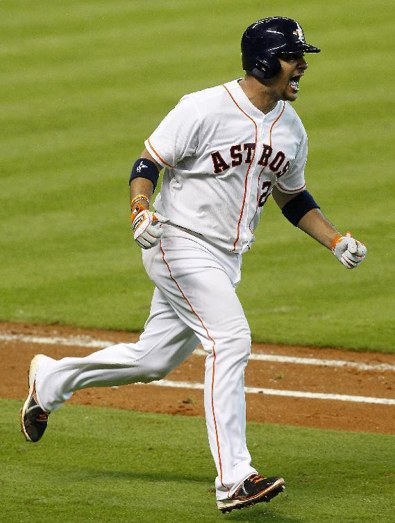 Houston Astros' Carlos Corporan (22) celebrates as he runs to first after hitting a home run scoring teammate Jason Castro in the sixth inning of a baseball game against the Oakland Athletics, Wednesday, July 24, 2013, in Houston. (AP Photo/Patric Schneider)