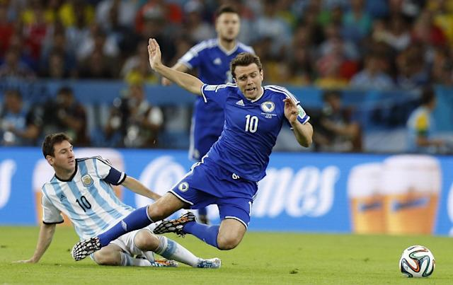 Argentina's Lionel Messi, left, fouls Bosnia's Zvjezdan Misimovic during the group F World Cup soccer match between Argentina and Bosnia at the Maracana Stadium in Rio de Janeiro, Brazil, Sunday, June 15, 2014. (AP Photo/Victor R. Caivano)