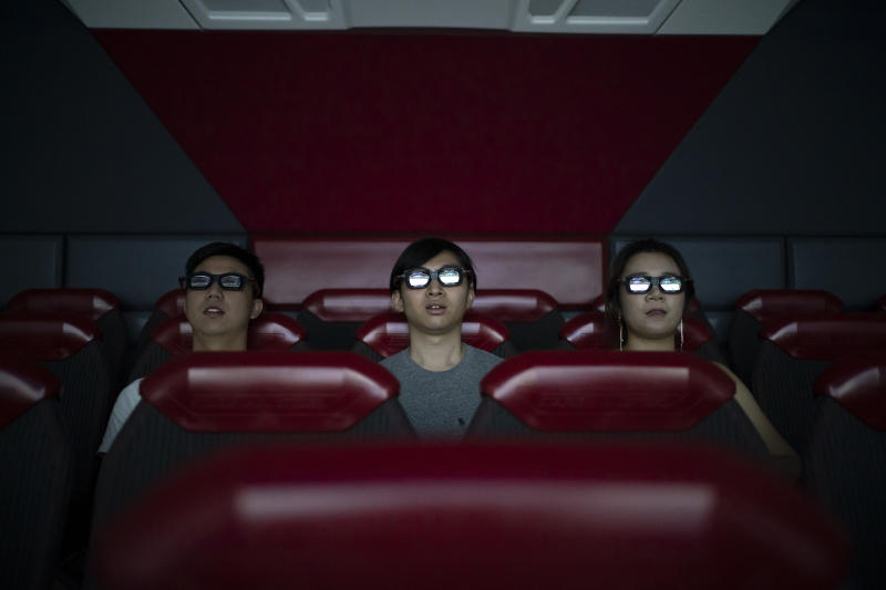 In this Oct. 11, 2019 photo, people watch a 3D movie part of the Iron Man Experience at Hong Kong Disneyland in Hong Kong. The body-blow of months of political protests on Hong Kong's tourism is verging on catastrophic for one of the world's great destinations. Geared up to receive 65 million travelers a year, the city's hotels, retailers, restaurants and other travel-oriented industries are suffering. But some intrepid visitors came specifically to see the protests and are reveling in deep discounts and unusually short lines at tourist hotspots.(AP Photo/Felipe Dana)