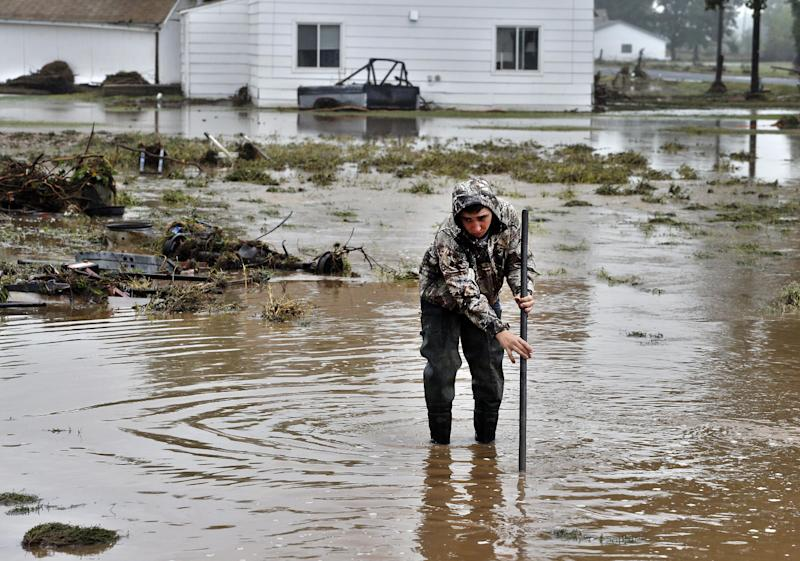 CORRECTS SPELLING OF CITY TO HYGIENE INSTEAD OF HYGEINE - Local man Joey Schendel, 19, looks for submerged items while helping neighbors salvage and clean their property in an area inundated after days of flooding, in Hygiene, Colo., Monday Sept. 16, 2013. Searches continue for missing people in isolated Colorado mountain towns. (AP Photo/Brennan Linsley)