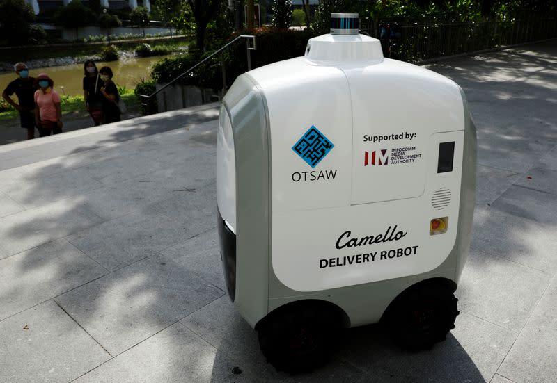 People look on as Carmello, an autonomous grocery delivery robot, makes its way during a delivery in Singapore