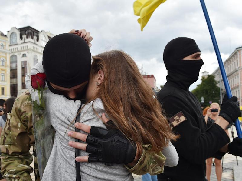 A girl cries as she embraces her boyfriend, a new volunteer recruit of the Ukrainian army 'Azov' battalion heading towards the eastern regions, after a military oath ceremony in Kiev, on June 23, 2014
