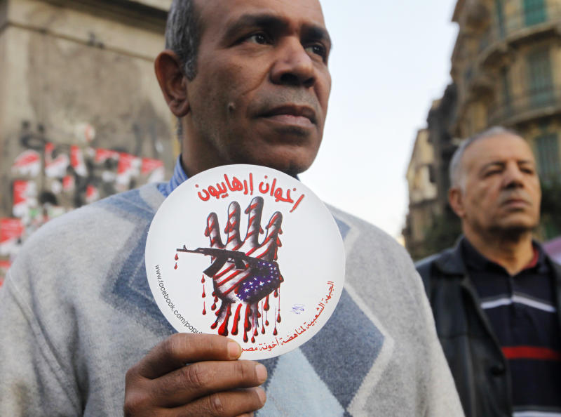 """An Egyptian activist holds a cardboard piece with an anti-terrorism picture and Arabic that reads, """"terrorists brotherhood,"""" during an anti-terrorism demonstration in Cairo, Egypt, Thursday, Dec. 26, 2013. A bomb blast hit a public bus in the Egyptian capital, wounding several people, the Interior Ministry said, in an attack that raised concerns that a wave of violence blamed on Islamic militants that has targeted security forces and military for months is increasingly turning to hit civilians. (AP Photo/Amr Nabil)"""
