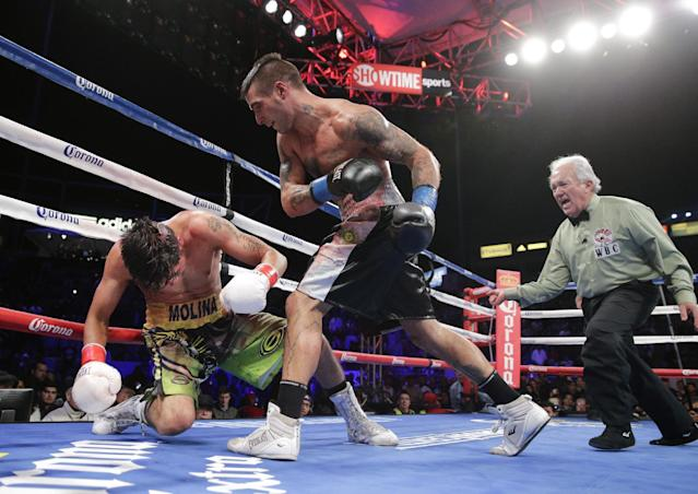 Lucas Matthysse, center, of Argentina, knocks down John Molina Jr. during the 11th round of a junior welterweight boxing match Saturday, April 26, 2014, in Carson, Calif. Matthysse won by knockout in the 11th round. (AP Photo/Jae C. Hong)