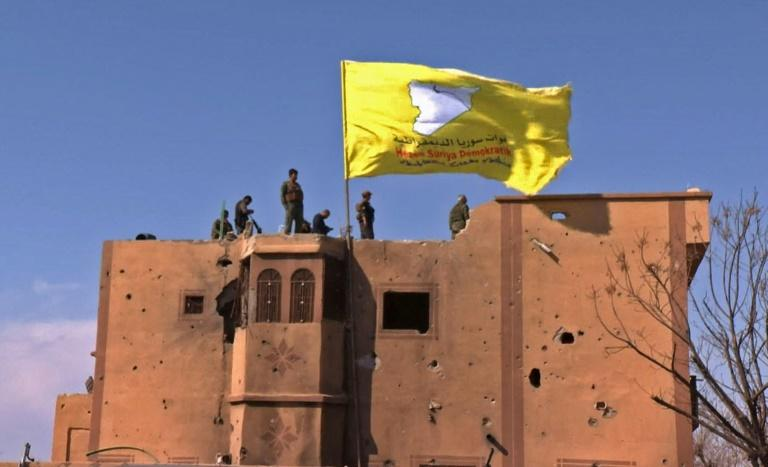 """US-backed fighters of the Syrian Democratic Forces raise their flag in the Islamic State group's last redoubt of Baghouz as their commanders proclaim the total elimination of its """"caliphate"""""""