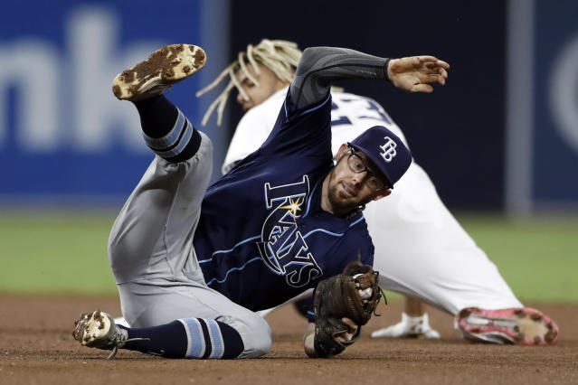 Tampa Bay Rays second baseman Eric Sogard, front, lands after tagging out San Diego Padres' Fernando Tatis Jr., who was caught stealing second base during the fourth inning of a baseball game Tuesday, Aug. 13, 2019, in San Diego. (AP Photo/Gregory Bull)