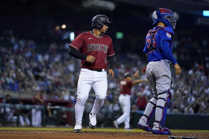 Arizona Diamondbacks' Eduardo Escobar, left, scores a run as Chicago Cubs catcher Robinson Chirinos, right, waits for a late throw during the fourth inning of a baseball game, Sunday, July 18, 2021, in Phoenix. (AP Photo/Ross D. Franklin)