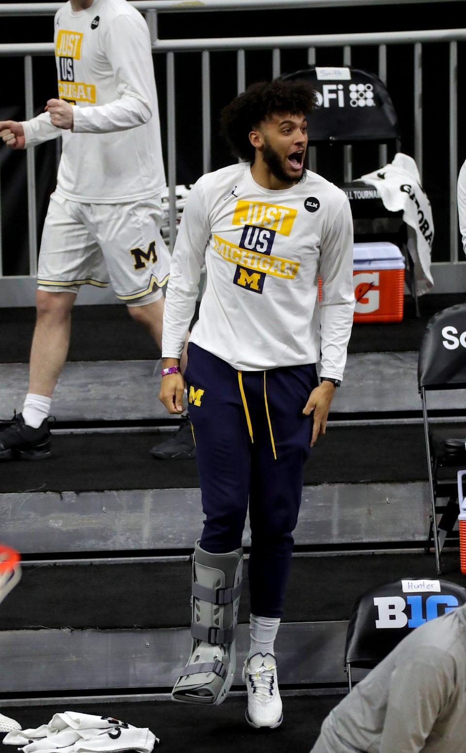 Michigan's Isaiah Livers, out with a foot injury, cheers during the Big Ten tournament semifinal against Ohio State on Saturday, March 13, 2021 at Lucas Oil Stadium in Indianapolis.