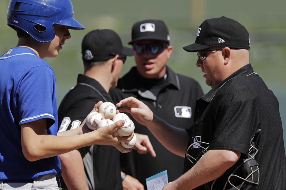 Home plate umpire Todd Tichenor, right, is handed a bunch of baseballs by a ballboy before a spring training baseball game between the Los Angeles Angels and the Kansas City Royals, Friday, March 6, 2020, in Surprise, Ariz. (AP Photo/Elaine Thompson)
