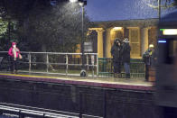 People wait for an arriving Long Island Rail Road train in the Queens borough of New York as snow starts to fall, Wednesday, Dec. 16, 2020. (AP Photo/Frank Franklin II)