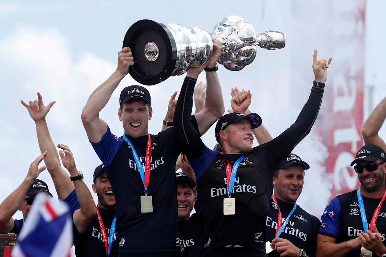FILE PHOTO - Sailing - America's Cup finals - Hamilton, Bermuda - June 26, 2017 - Peter Burling, Emirates Team New Zealand Helmsman celebrates with Skipper Glenn Ashby as they hold the America's Cup trophy after defeating Oracle Team USA. REUTERS/Mike Segar/File Photo